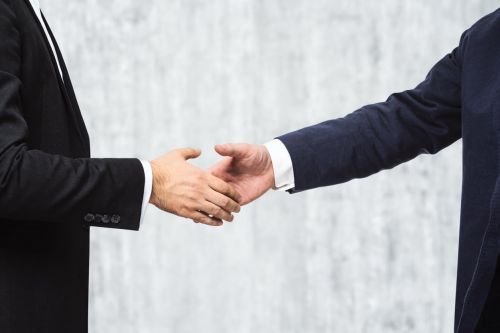 Insider Trading Concept - Businessmen shaking hands